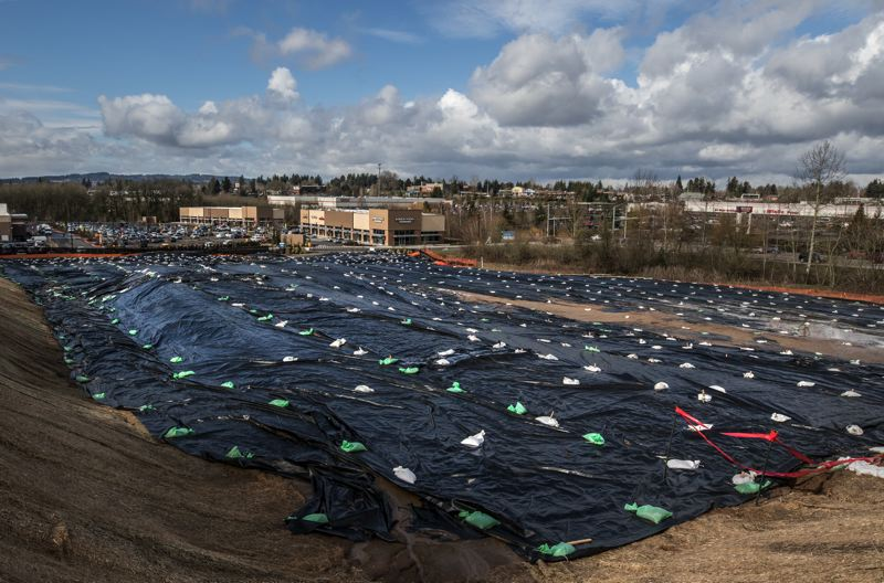 TIMES PHOTO: JONATHAN HOUSE - Large tarps cover an open lot near Walmart in the Tigard Triangle.