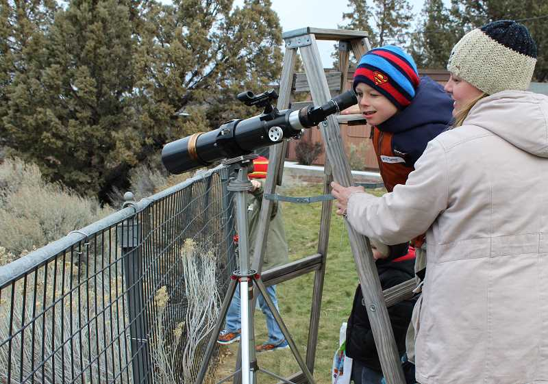 HOLLY M. GILL - Mandi Oelrich, of Madras, helps her son, Kaleb, 8, look through a spotting scope into the Deschutes River Canyon, above the Cove Palisades Park and Round Butte Dam at the 22nd annual Eagle Watch on Sunday, at Round Butte Overlook Park. Two other sons, Kory, 7, and Kayden, 4, await their turns.