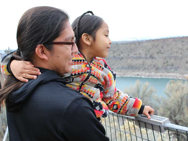 HOLLY M. GILL - Frank Stwyer, left, holds his brother, JoeRay, 5, up to look out over the Pelton Dam area from Pelton Overlook Park on Sunday, at the 22nd annual Eagle Watch, held Feb. 25 and 26.