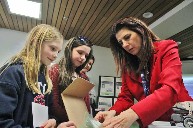REVIEW PHOTO: KELSEY OHALLORAN - Evergreen Aviation and Space Museum Education Director Hilda Pereyo (right) shows educational LEGO kits to St. Thomas More Catholic School fifth-graders Quinn Flanagan (left) and Sarah Wolff. Evergreen offers camps and workshops connected to the LEGO sets.