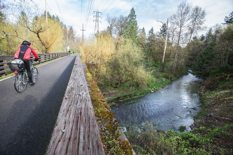 TRIBUNE FILE PHOTO  - A bicyclist pedals over Johnson Creek on the Springwater Corridor Trail.