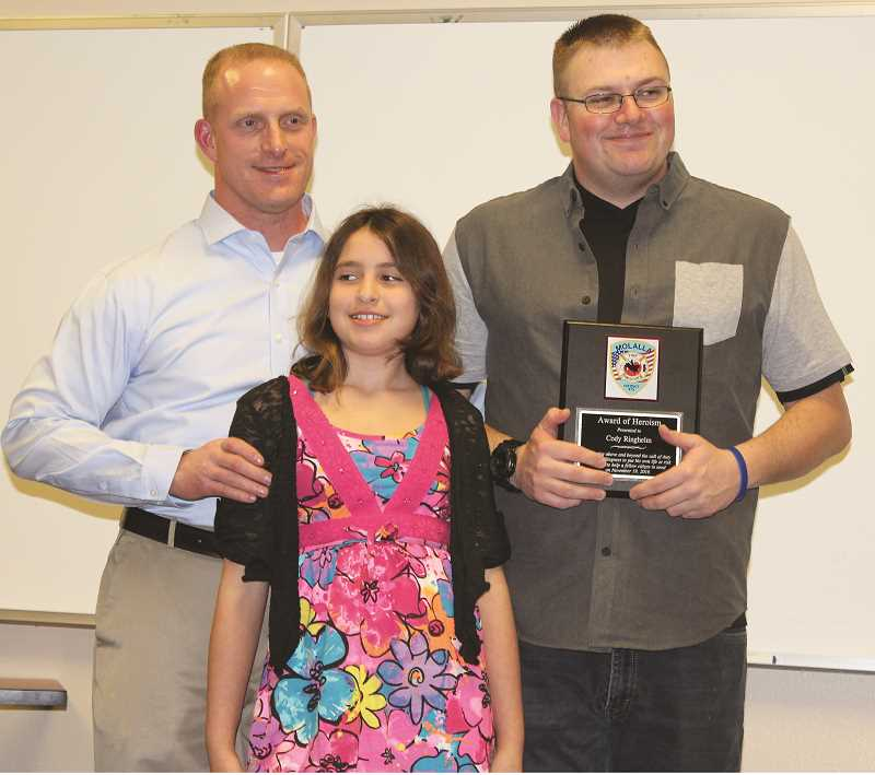 PEGGY SAVAGE - Anthony Kollias, left, and his daughter, Elia, 10, with Cody Ringheim, who recieved the Award of Heroism for actions 'Above and Beyond the call of duty.'