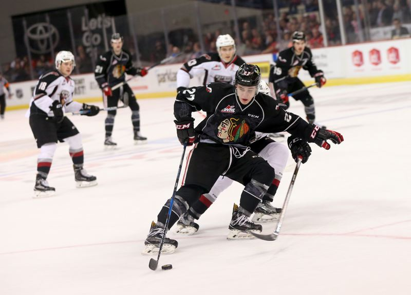 COURTESY: BRYAN HEIM/PORTLAND WINTERHAWKS - Portland Winterhawks forward Brad Ginnell protects the puck against the Vancouver Giants on Friday night at Memorial Coliseum.