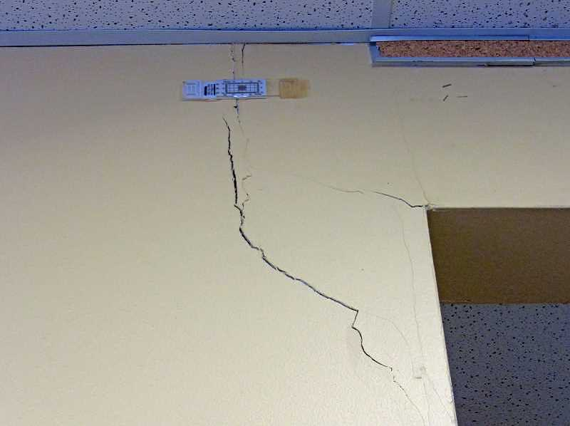 REVIEW FILE PHOTO: VERN UYETAKE - A fissure at Lakeridge Junior High School is measured with a crack meter. The school is slated for replacement in the May school bond because it sits on shifting soil and has widening cracks in its walls and foundation.