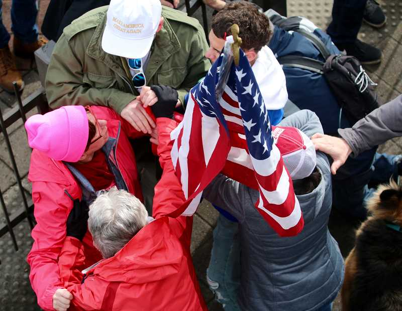 REVIEW PHOTO: BRIAN MONIHAN - 'Stand for LOve' participants clash toward the end of the day Saturday with Trump supporters near the gates that seperate the train tracks on State Street from stairs leading to Millennium Plaza Park. A 76-year-old West Linn resident was overcome during the confrontation and had to be transported by ambulance to a local hospital.