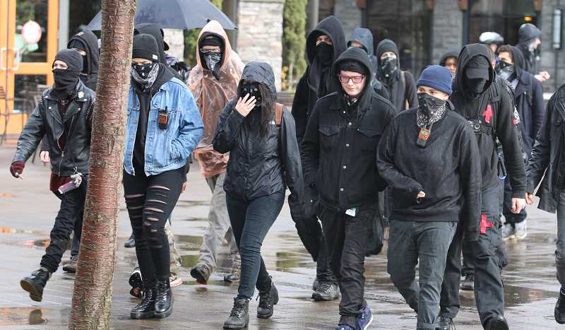 REVIEW PHOTO: BRIAN MONIHAN - Protesters wearing ski masks and bandanas over their faces head towards the 'Stand for LOve' rally at Millennium Park Plaza.