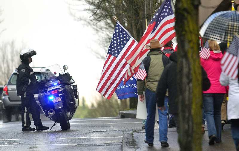 REVIEW PHOTO: VERN UYETAKE - Police keep watch as the 'March 4 Trump' heads down State Street on Saturday in Lake Oswego.