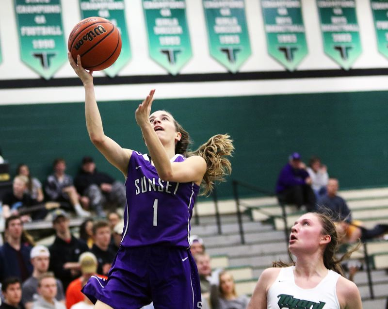 DAN BROOD - Sunset junior Delaney Ragan goes up to the basket in front of Tigard sophomore Campbell Gray.
