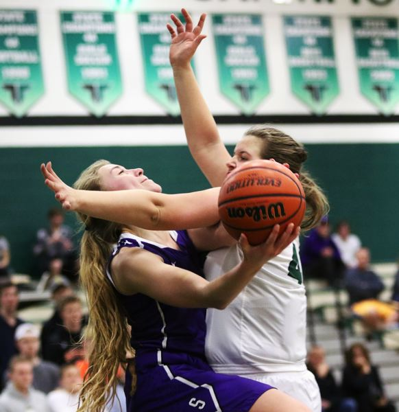 DAN BROOD - Sunset senior Claire Salness (left) is fouled by Tigard sophomore Dani Lyons as she tries to go up to the basket in Saturday's state playoff game.