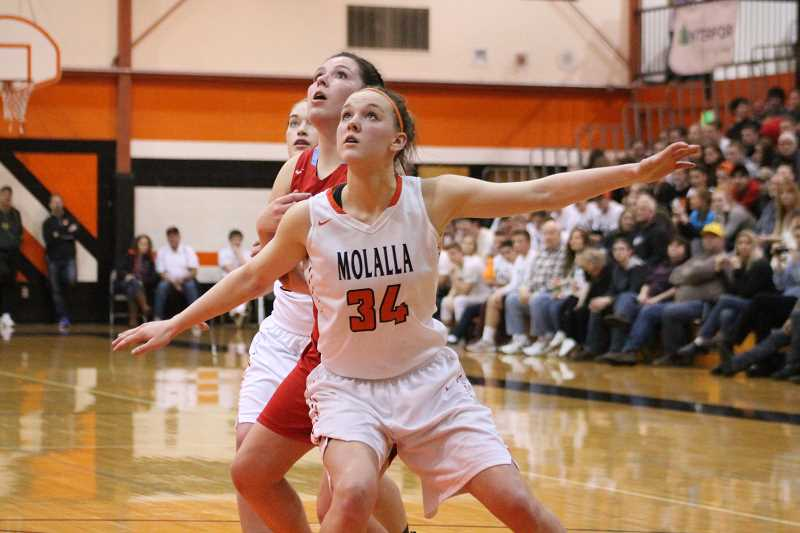 PIONEER PHOTO: CONNER WILLIAMS - Molalla junior Alicia Schultz boxes out a Seaside defender during the Indians' 38-31 loss in the first round of the Class 4A playoffs at home last Saturday.