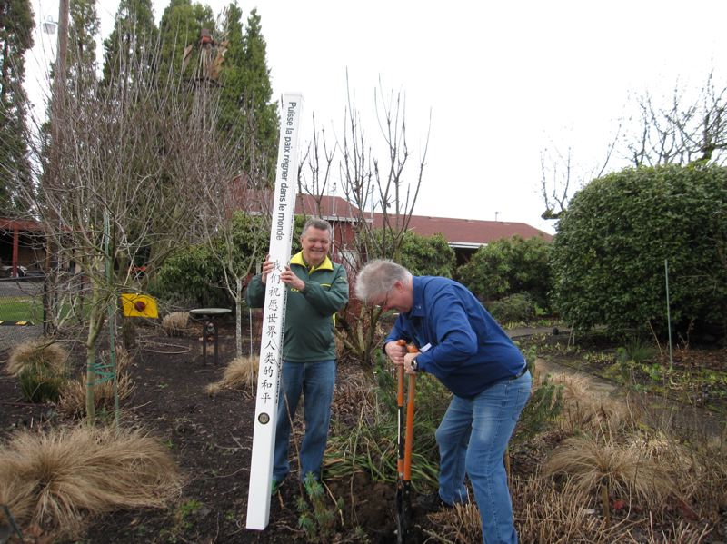 SUBMITTED PHOTO - Phil James holds the pole while David Potts digs a hole to plant the Rotary Club of Milwaukie's first Peace Pole on Feb. 26 at the Milwaukie Wellness Center
