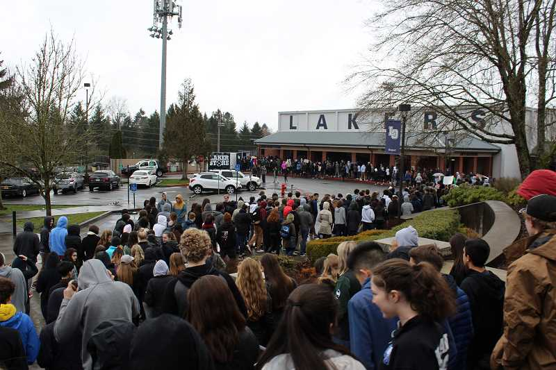 REVIEW PHOTO: JILLIAN DALEY - Lake Oswego High School students pour out of the school in support of acceptance of all races during a walkout Tuesday morning.