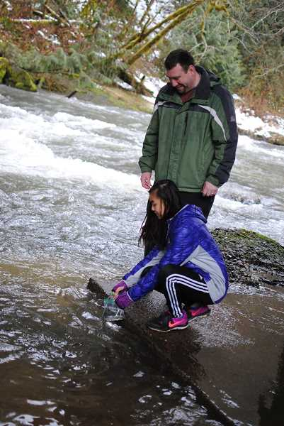 NEWS-TIMES PHOTO: STEPHANIE HAUGEN - Middle school science teacher Ben Bauer helped Katie Abrahamson released the baby fish into the stream.
