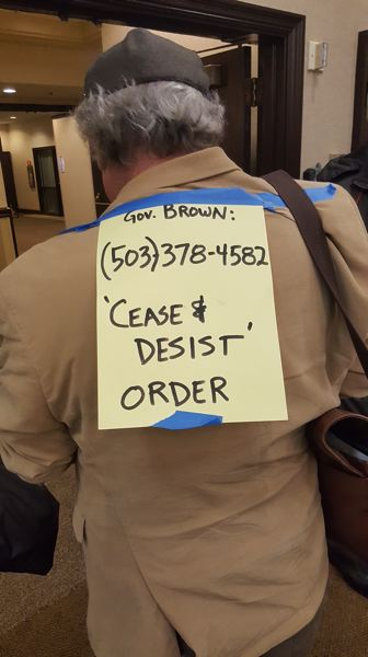 FOR THE TRIBUNE: PAUL KOBERSTEIN - Mark Thommen of Hayden Island wore a message for the governor on his back at the meeting.
