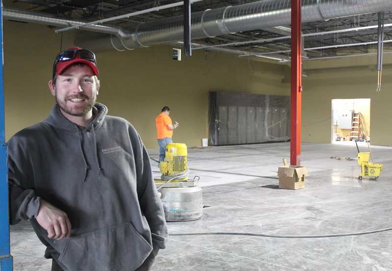 HOLLY M. GILL - James Bultena, project manager for Dickerhoof Construction, oversees the polishing of the concrete floors at the new Grocery Outlet on Monday. The store is expected to open April 13.