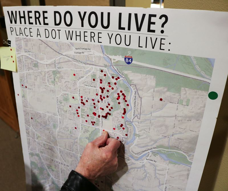 FILE PHOTO - A man places a dot where he lives during a Metro-hosted trail route open house last month.