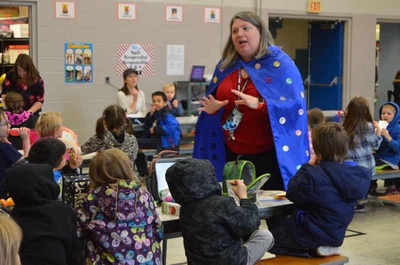SPOTLIGHT PHOTO: NICOLE THILL - Grant Watts Principal Jen Stearns quizzes students on how to count to 100 during a lunchtime activity. Stearns also wore a superhero cape covered in 100 good behavior tokens to make the day festive.