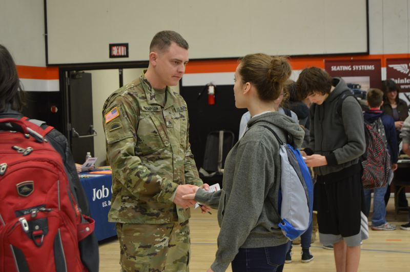 SPOTLIGHT PHOTO: NICOLE THILL - Jesse Thompson from the Oregon Army National Guard speaks with Alexa Morkert during the career expo. Although she is only a freshman, Mokert said she is considering joining the military after she graduates high school.