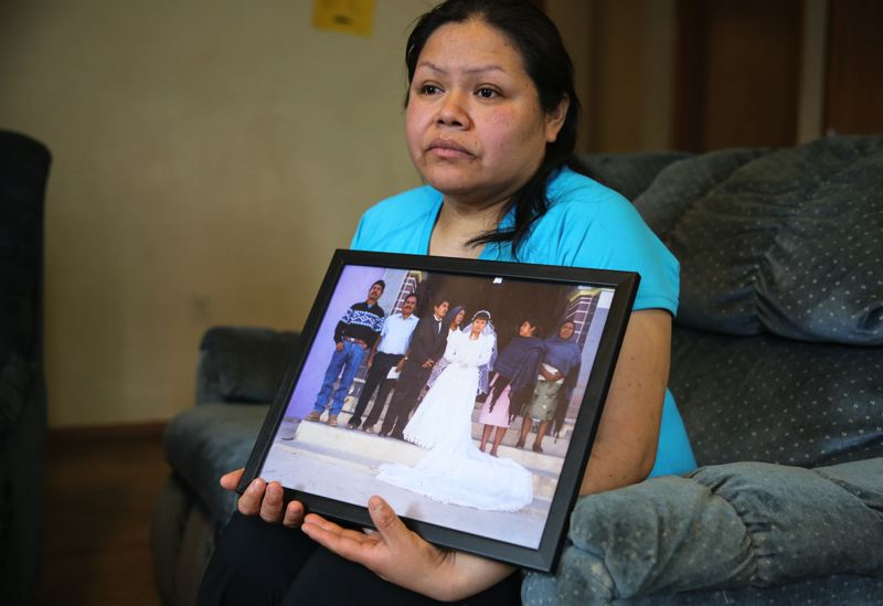 OPB PHOTO - Rosalina Guzman holds a photo of her and her husband, Roman, from their wedding day.