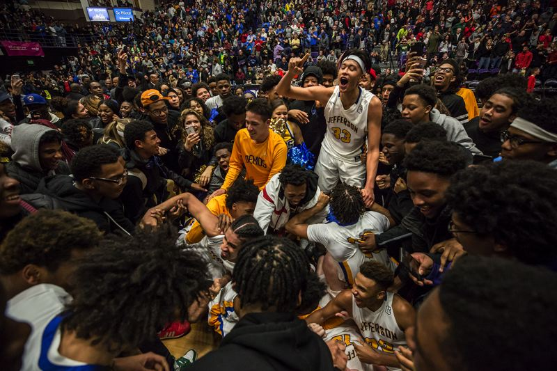 TRIBUNE PHOTO: JONATHAN HOUSE - The Jefferson Democrats and fans celebrate at Chiles Center after the team defeated Clackamas 70-67 to win the Class 6A boys basketball championship on Saturday.