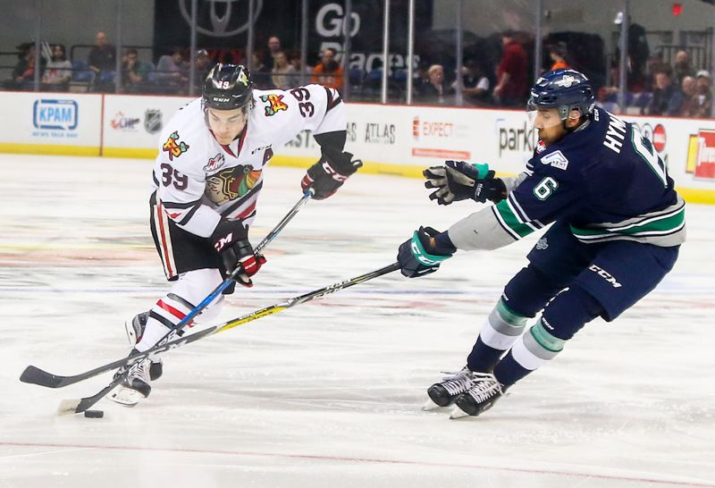 COURTESY: DAYNA FJORD/PORTLAND WINTERHAWKS - Portland Winterhawks forward Colton Veloso aims the puck past Thunderbirds defenseman Aaron Hyman in a game against Seattle Saturday at Memorial Coliseum.