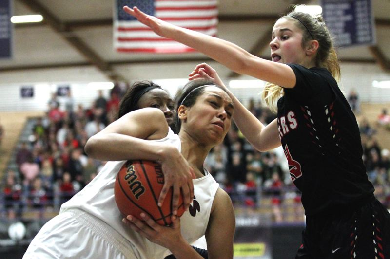 TIMES PHOTO: JAIME VALDEZ - Southridge junior power forward Natalie Hoff hauls down a rebound over Oregon City Pioneers  in the 6A girls basketball state championship at Chiles Center.