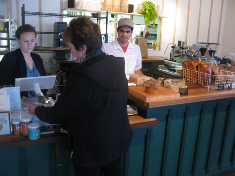PHOTO BY: RAYMOND RENDLEMAN - Grano Bakery co-owner Ava Mikolavich rings up a customer while fiance Ulises Alvarez looks on.