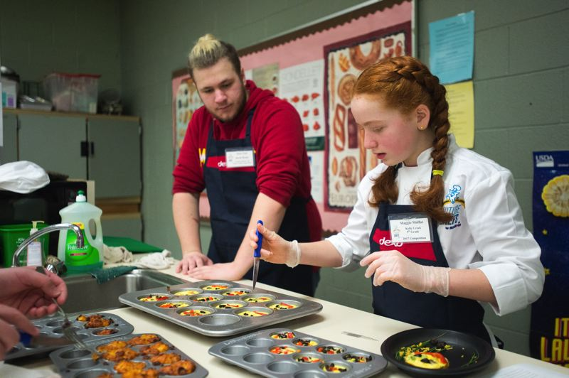 OUTLOOK PHOTO: JOSH KULLA - Kelly Creek Elementary fifth-grader Maggie Moffat prepares her Emoji egg cups for the Future Chefs competition as advisor Dylan Jackson, a Barlow High culinary student, looks on.