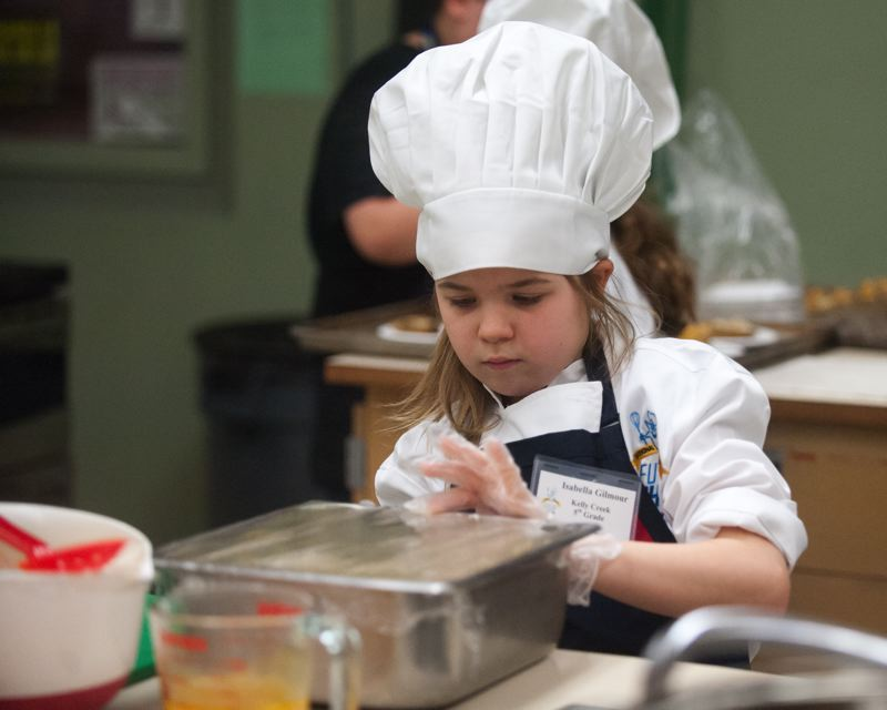 OUTLOOK PHOTO: JOSH KULLA - Kelley Creek Elementary fifth grader Isabella Gilmour works on her culinary creation prior to the judging portion of the competition.