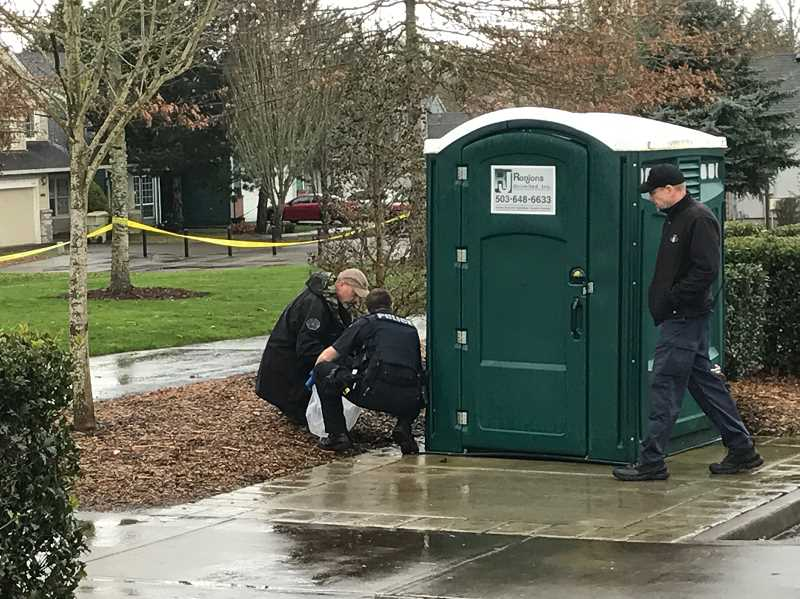 HILLSBORO TRIBUNE PHOTO: GEOFF PURSINGER - Hillsboro Police officers pick up debris from several bottles found at Reedville Park Tuesday morning that contained some type of explosive.