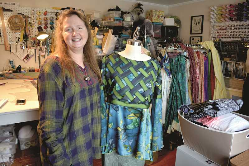 NEWS-TIMES/HILLSBORO TRIBUNE PHOTO: KATHY FULLER - Hillsboro resident Paula Smith-Danell stands next to one of the outfits she designed and created in her home studio.