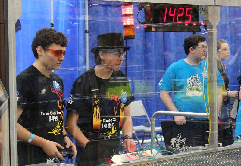 SPOKESMAN PHOTO: ANDREW KILSTROM - Error Code Xero's Andrew Kassab, left, drives the teams robot during qualification rounds.
