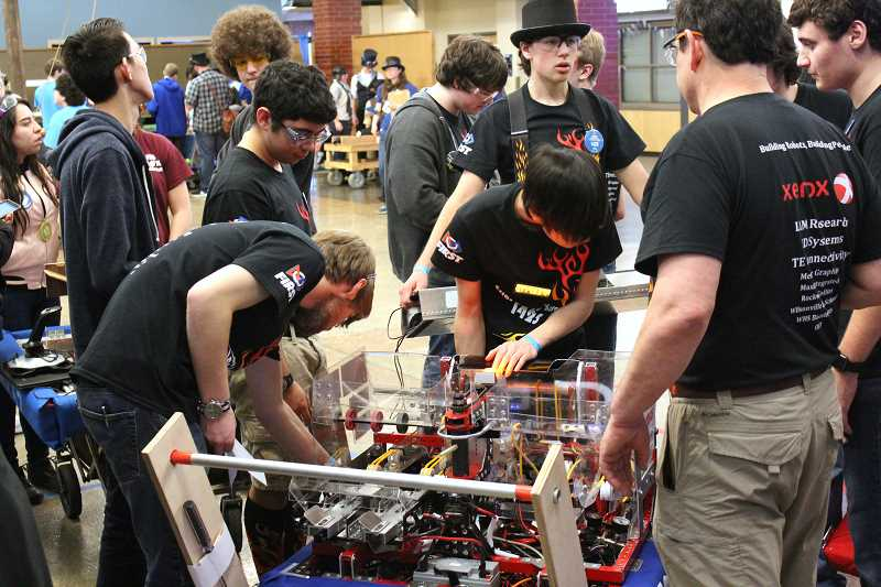 SPOKESMAN PHOTO: ANDREW KILSTROM - Members of the Error Code Xero electrical team make some adjustments in between qualification matches Friday, March 10.