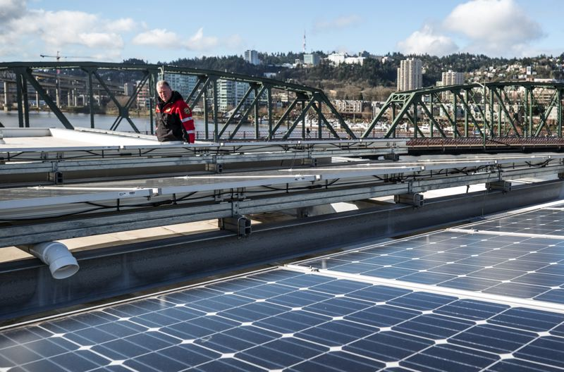 PAMPLIN MEDIA GROUP: JONATHAN HOUSE - Deputy Fire Chief Marco Benetti checks out the solar panels on the roof of Fire Station 21, on the Willamette River. The city has put panels on several stations.