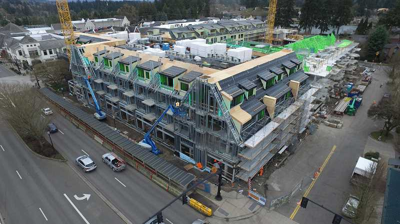 REVIEW PHOTO: ALVARO FONTAN - March 10, 2017: Despite what feels like nonstop rain, workers continue to install roofing, sheathing and flashing on Building A in this photo looking southeast from A Avenue and Second Street.