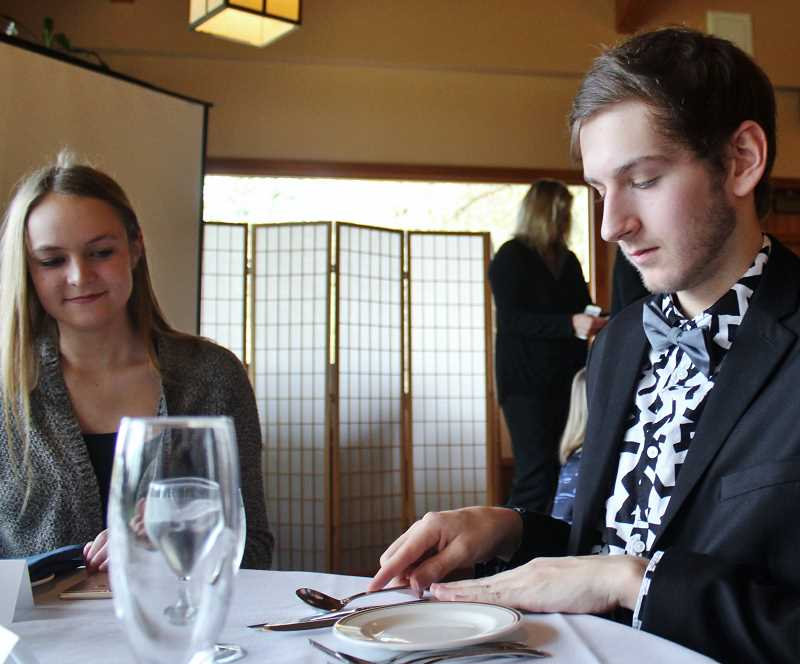 REVIEW PHOTO: KELSEY OHALLORAN - Lake Oswego High School junior Winston Moore arranges his table settings during an Etiquette Dinner on Sunday for the National League of Young Men.