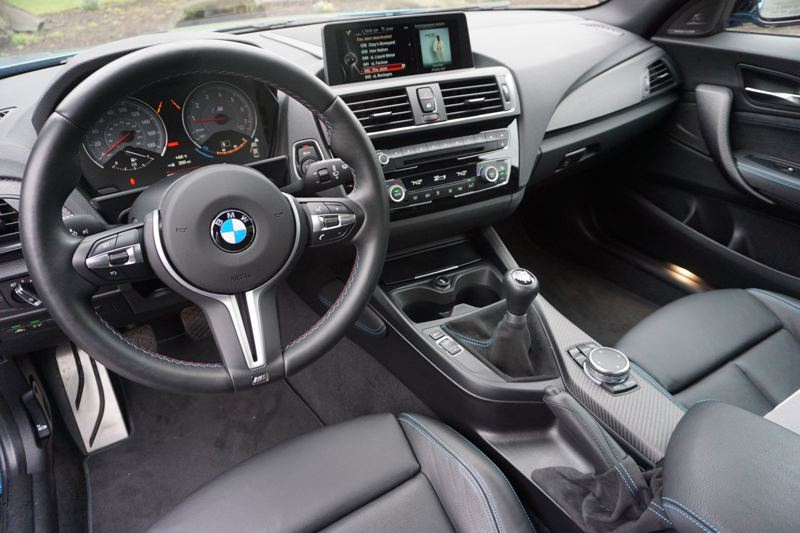 PORTLAND TRIBUNE: JEFF ZURSCHMEIDE - The interior of the 2017 BMW M2 has sporty carbon fiber touches rather than luxury trim and BMW's full technology suite with navigation, BMW iDrive, and a Harman Kardon stereo.