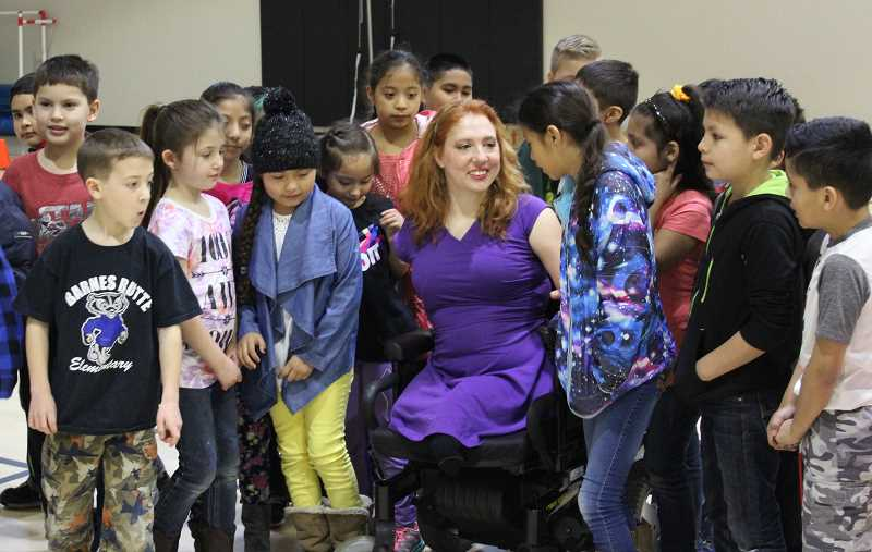 JASON CHANEY - Jennifer Adams spoke to children at Barnes Butte and Crooked River Elementary schools Wednesday. The nationally known motivational speaker, who was born with partial limbs, gave an anti-bullying and inclusion message, sang a song and showed her dancing skills. In the above photo, Adams chats with members of Kerry Lysne's second-grade class at Barnes Butte.