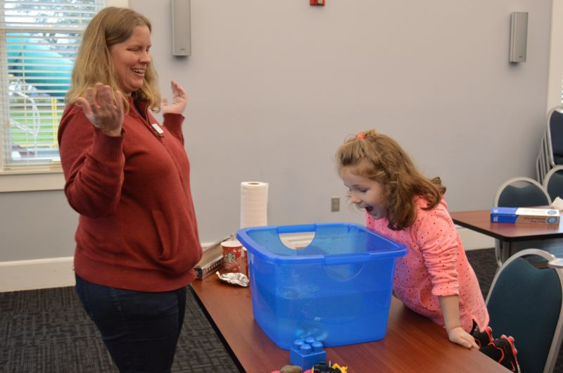 SPOTLIGHT PHOTO: COURTNEY VAUGHN - Callie Campbell, 4, watches as Wendi Andrews throws the final nickel on a small boat made of tin foil. The foil boat sank in water after being weighted with 68 pennies and 11 nickels. Campbell participated in a Science Explorers activity hour called 'What Makes Things Float?' at the Scappoose Public Library Tuesday, March 14.