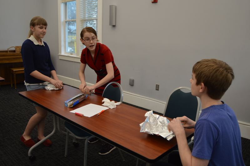 SPOTLIGHT PHOTO: COURTNEY VAUGHN - Library volunteers from Scappoose Middle School join in on a Science Explorers hour to construct makeshift boats out of aluminum foil and see how much weight they could hold before sinking. Pictured left to right: Madison Mobley, 13, Helen Connell, 13, and Matthew Myton, 13.
