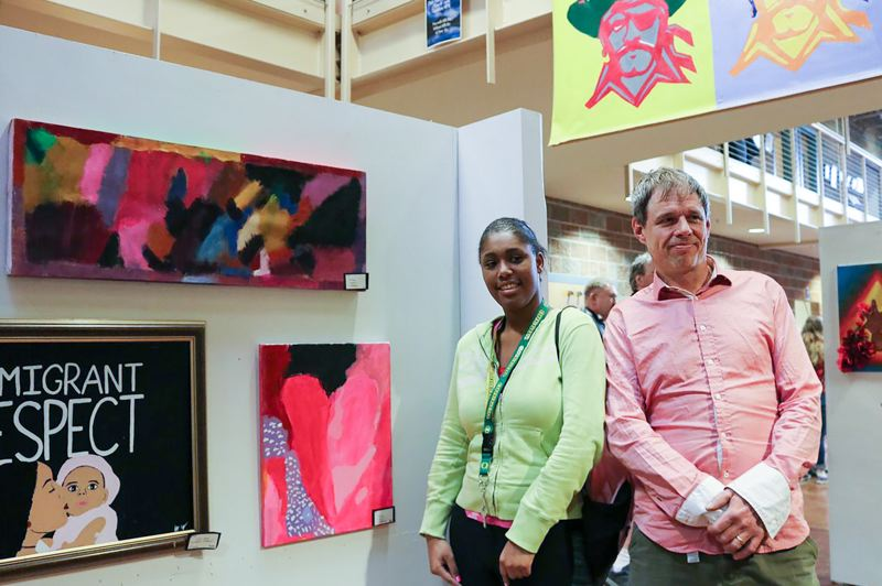 CONTRIBUTED - Kiara Willard, a student, and artist Benjamin Clark pose next to some of the art at the Reynolds art show.