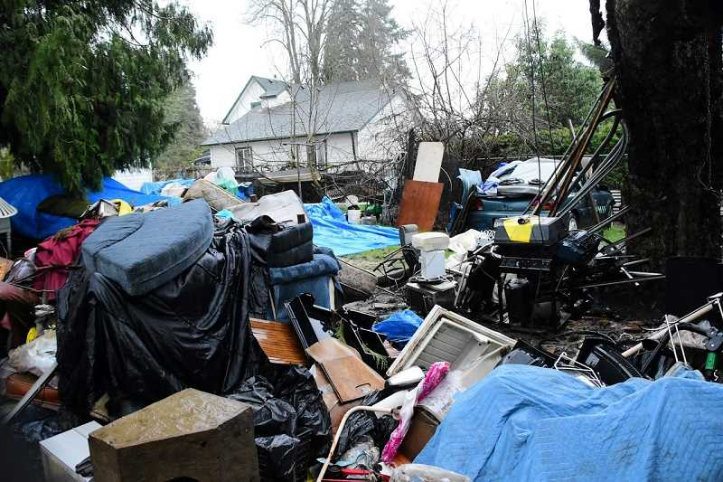 SUBMITTED PHOTO - Police removed 14 dump trucks worth of garbage and debris from a home in the 600 block of Southeast Third Avenue on Wednesday. Code enforcement had been working with property owners for nearly two years to clean up the site.
