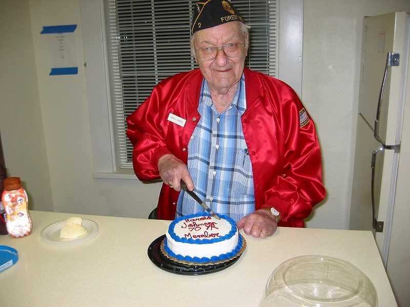 SUBMITTED PHOTO - Local veteran Harold Johnson cuts into his celebratory cake.