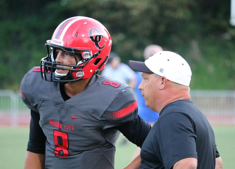 REVIEW/NEWS PHOTO: JIM BESEDA - Oregon City quarterback DeQuahn Dennis-Lee listens to instructions from Pioneers coach Randy Nyquist during last season's jamboree at Pioneer Memorial Stadium.