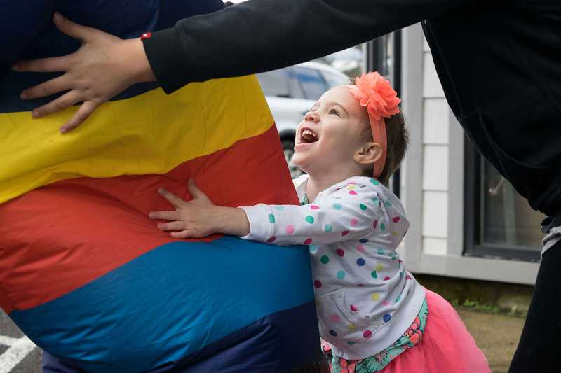 NEWS-TIMES PHOTO: TANNER BOYLE - Gracie Corrigan loves the giant inflatable flailing-arm figure that marked the event.