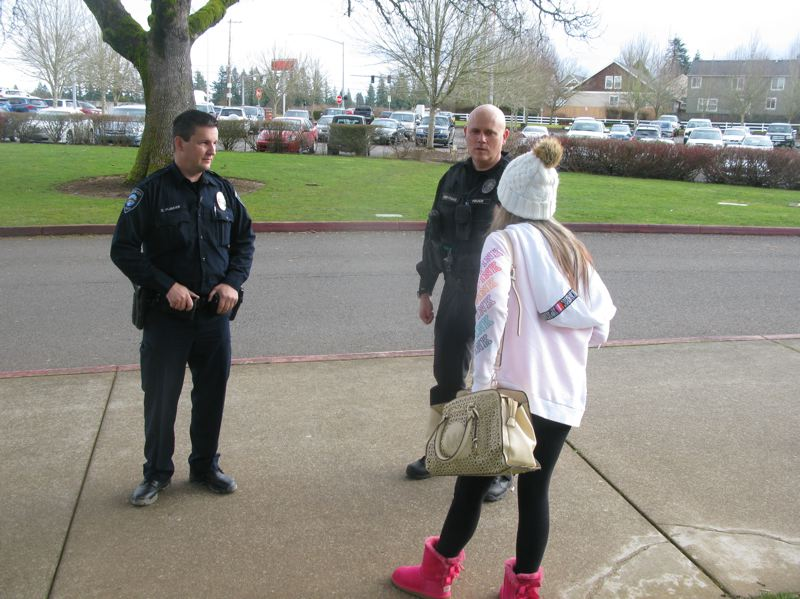 PHOTO BY: RAYMOND RENDLEMAN - David Plummer (left) and Steve Heryford, OCPD's two school resource officers, talk with a student outside of Oregon City High School.
