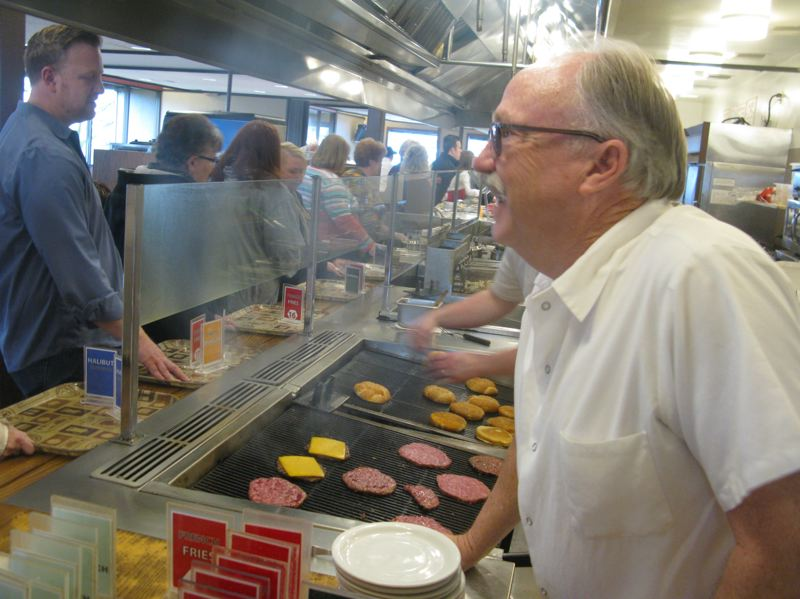 PHOTO BY: RAYMOND RENDLEMAN - Tebo's co-owner Craig Klein talks with customers as he works the grill.