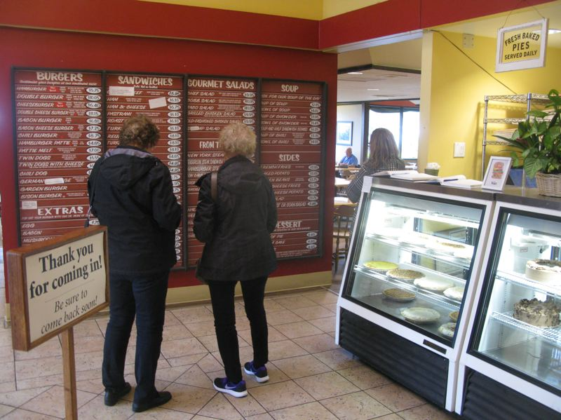 PHOTO BY: RAYMOND RENDLEMAN - Tebo's Restaurant customers pause in front of the large wooden bulletin board that serves as a menu in front of the pie displays.