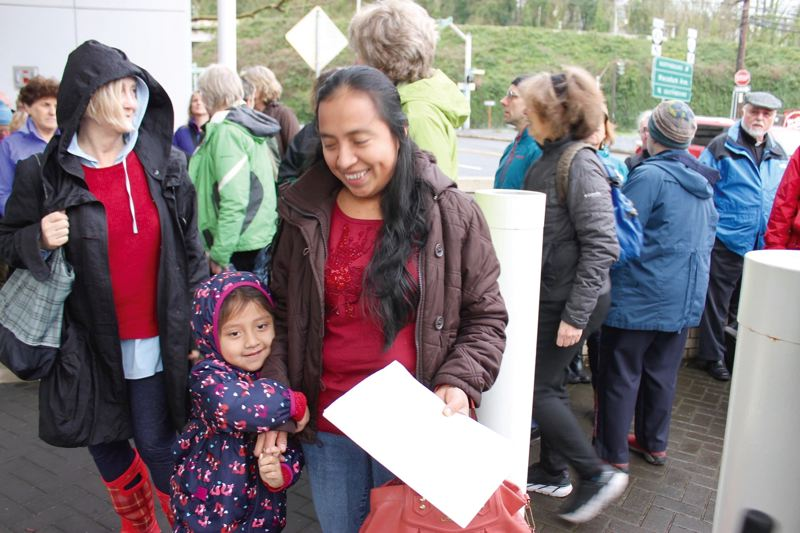 TRIBUNE PHOTO: LYNDSEY HEWITT - Belinda Miranda de Solano with her daughter, Genesis, 3, checked in at the Immigration and Customs Enforcement (ICE) office at 4310 S.W. Macadam Ave. last week while activists stood in support. As of the end of February, there were 4,337 pending immigration cases in Portland, according to the Executive Office for Immigration Review. Solano's next check-in is on Sept. 20.