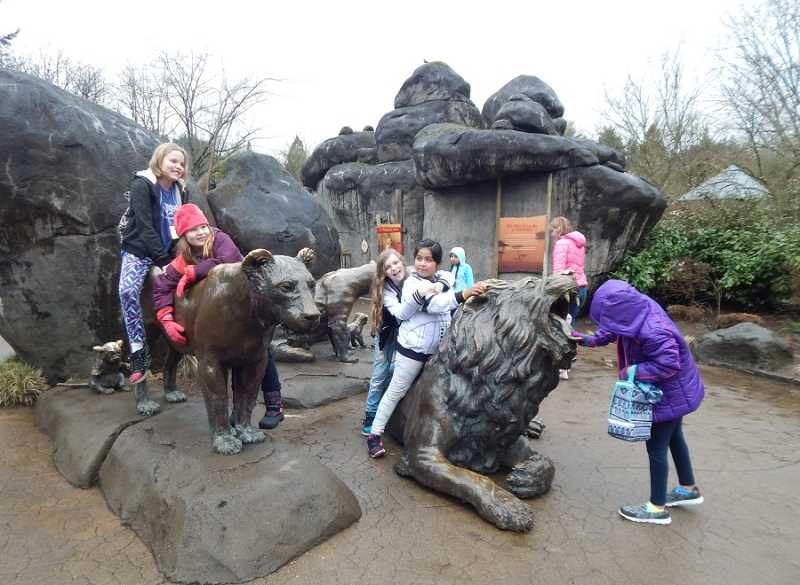 REGAL COURIER PHOTO: BARBARA SHERMAN - On a cold and rainy day at the Oregon Zoo, the lion sculptures were more fun than the real lions tucked away in their cozy den; from left are Emma, Kimberly, Kylie, Linda, Jennifer (in background) and Rinret.